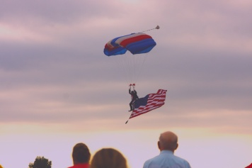 The crowd watches a man come down from the sky with a parachute during an air show in Sidney, Montana.